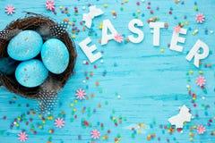 Ostereier im Nest auf blauem Hintergrund mit buntem Ostern-deco Lizenzfreies Stockbild