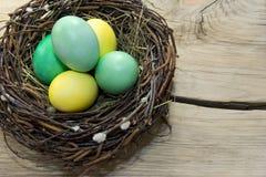 Ostereier im Nest auf hölzernem Hintergrund Lizenzfreie Stockbilder