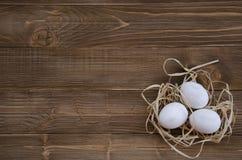 Ostereier im Nest auf hölzernem Hintergrund Lizenzfreies Stockfoto