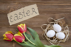 Ostereier im Nest auf hölzernem Hintergrund Stockfotos