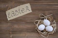 Ostereier im Nest auf hölzernem Hintergrund Lizenzfreie Stockfotografie