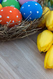Ostereier im Nest sind auf dem Tisch mit gelben Tulpen Stockfotografie