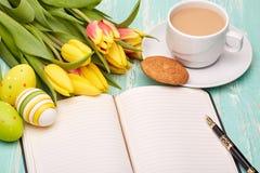 Ostereier, leerer täglicher Klotz und Tulpen Stockfoto