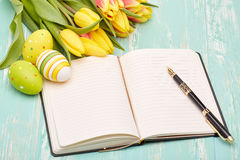 Ostereier, leerer täglicher Klotz und Tulpen Lizenzfreies Stockbild