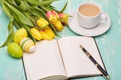 Ostereier, leerer täglicher Klotz und Tulpen Stockfotografie