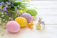 Ostereier mit Blumen und Kaninchenspielwaren auf einem weißen Holztisch Lizenzfreies Stockfoto