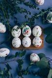 Ostereier mit Blumenverzierung auf blauer Tabelle stockfotografie