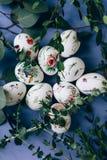 Ostereier mit Blumenverzierung auf blauer Tabelle stockfoto