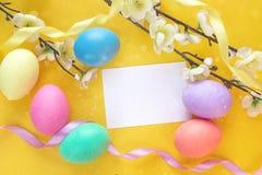 Ostereier mit Karte des leeren Papiers und Apfelbaumast auf yello Lizenzfreies Stockbild