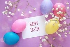 Ostereier mit Karte des leeren Papiers und weiße Blumen auf purpurrotem Ba Stockbild