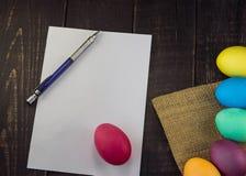 Ostereier mit leerem Papier und Stift auf Holztisch Bereiten Sie zu vor Stockfotografie