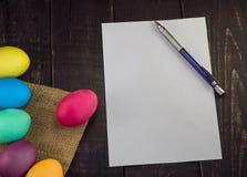 Ostereier mit leerem Papier und Stift auf Holztisch Glückliches Eas Lizenzfreie Stockbilder