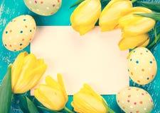 Ostereier, Tulpen und Karte stockfoto