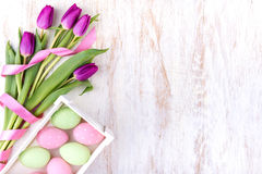 Ostereier und Blumen über weißem Holztisch Stockfoto
