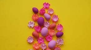 Ostereier und Blumen gemacht vom Papier auf einem gelben Hintergrund Die Farben sind rosa, Burgunder, Fuchsie und Gelb Frühling stockfotografie