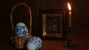 Ostereier und eine brennende Kerze in einem Kerzenständer vor einer Ikone von Jesus Christ stock video
