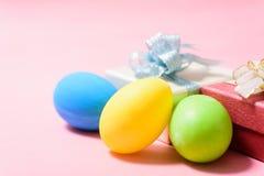 Ostereier und Geschenkbox auf rosa Hintergrund Lizenzfreie Stockfotos