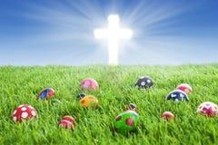 Ostereier und Kreuz auf Gras Stockfotos