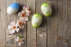 Ostereier und Mandel blühen auf altem Holztisch Stockfoto