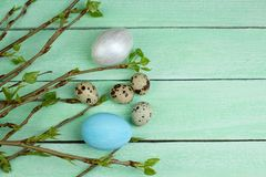Ostereier und Niederlassung mit Blättern auf Holztischhintergrund Beschneidungspfad eingeschlossen Kopieren Sie Raum für Text Lizenzfreies Stockfoto