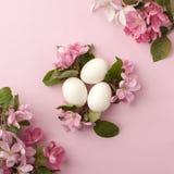 Ostereier und rosa Blumen auf weißem Hintergrund Ostern-Nest Ebenenlage, Draufsicht, Konzept des Frühlinges, Weiblichkeit und Sch Stockfotos