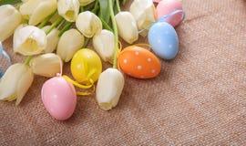 Ostereier und Tulpen auf einer Leinwand Stockfotografie