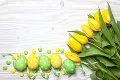 Ostereier und Tulpen auf hölzernem Hintergrund Lizenzfreies Stockfoto