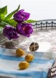 Ostereier und violette Tulpen auf Weinlesesilbertablett stockbilder