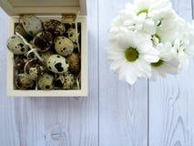 Ostereier und weiße Blumen auf einem weißen Holztisch Stockfotografie