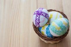 Ostereier verziert in einem Weidenkorb auf einem hölzernen Hintergrund Stockbilder