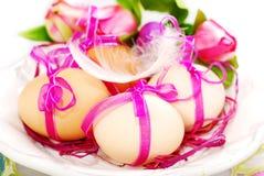 Ostereier mit rosa Band auf der Platte Lizenzfreies Stockbild