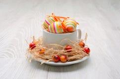 Ostereier verziert mit Stroh und kleinen wilden Äpfeln Stockfotografie