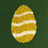 Ostereiform mit Frühling blüht auf einer grünen Wiese Stockbilder