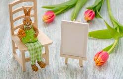Osterhase, der auf dem Schemel mit einem Ei, einem malenden Gestell und Tulpen über hölzernem Hintergrund sitzt Lizenzfreie Stockfotografie