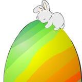 Osterhase, der auf einem Ei schläft Lizenzfreie Stockbilder
