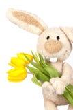 Osterhase, der Tulpen anhält Stockfotografie