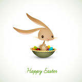Osterhase, der voll in der Schüssel farbigen Eiern sitzt Stockbilder