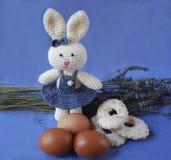 Osterhase mit Eiern und Keksen auf Lavendelhintergrund Lizenzfreies Stockfoto