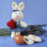 Osterhase mit rotem Herzen, Ei, Kekse auf Lavendelhintergrund Lizenzfreies Stockfoto
