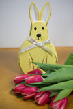 Osterhase mit Tulpen, gelber Hintergrund Stockfoto
