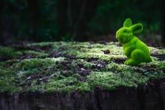 Osterhase sitzt auf einem Baumstamm stockfotos