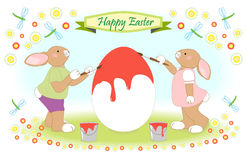 Osterhasenfamilie, die großes Ei malt Stockfoto