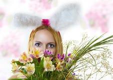 Osterhasenfrau, die über Blumen schaut Stockfoto