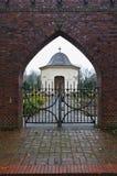Osterholz-Scharmbeck, Alemania - 3 de diciembre de 2017 - visión a través de la puerta del cementerio hacia la capilla fúnebre fotos de archivo