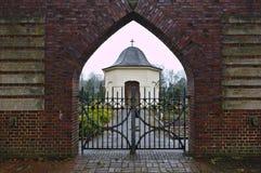 Osterholz-Scharmbeck Tyskland - December 3rd, 2017 - sikt till och med kyrkogårdporten in mot det begravnings- kapellet Arkivbild