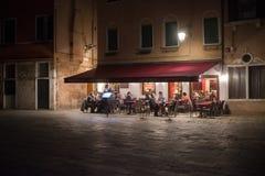 Osteria en la noche en una plaza local en una vecindad veneciana imágenes de archivo libres de regalías