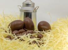 Ostern auf dem Bauernhof, den Milchprodukten, den Schokoladeneiern und dem altmodischen Milchkrug stockfotografie