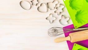 Ostern backen Werkzeuge mit Plätzchenschneider, Kuchenform für Muffin und kleinem Kuchen auf weißem hölzernem Hintergrund, Draufs Stockfoto