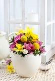 Ostern-Blumengesteck im Oberteil des weißen Eis Stockfotografie