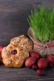 Ostern-Brot mit Samen des indischen Sesams, farbigen Eiern und Gras Stockfotos